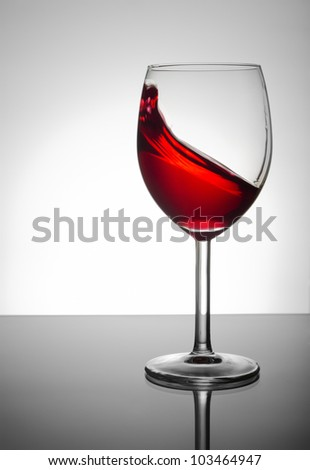 Wineglass with red wine splashing - stock photo