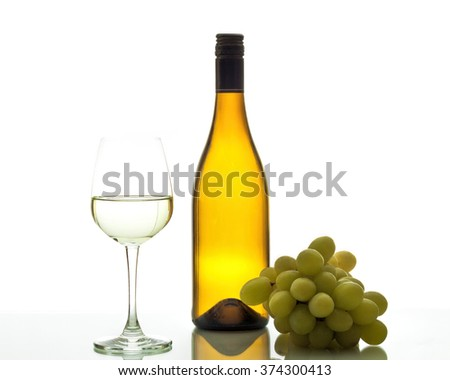 Wineglass with white wine and grapes. - stock photo