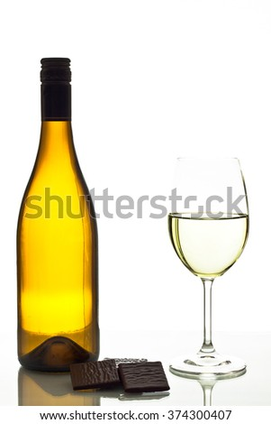 Wineglass with white wine with chocolate. - stock photo