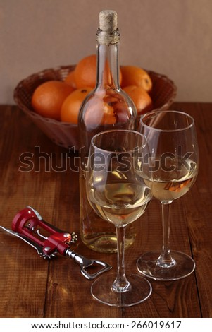 Wineglasses, bottle of white wine, corkscrew and orange fruits in basket on wooden table - stock photo