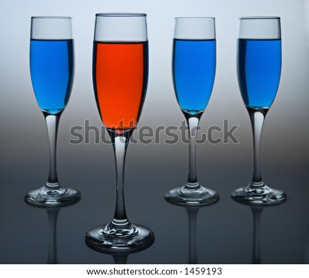 Wineglasses filled with colored liquid - illustrating concepts such as Workplace Diversity, Democrat versus Republican, or Dare to be Different. - stock photo