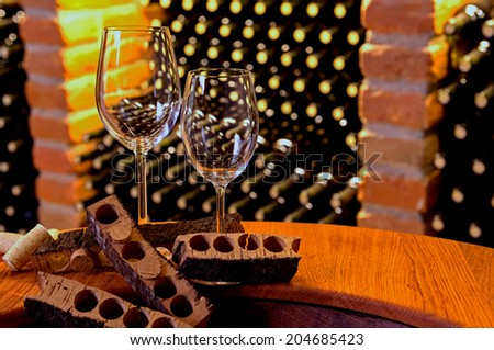 wineglasses with cork stoppers and cork bark standing in front of brick boxes of bottles of wine - stock photo