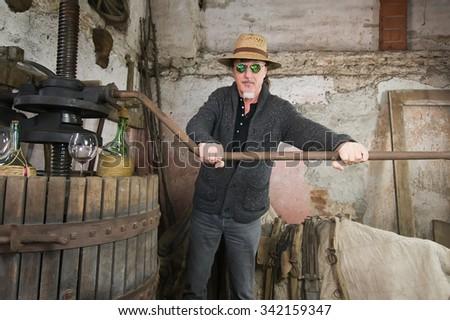 winemaker next to old press looking at camera - stock photo