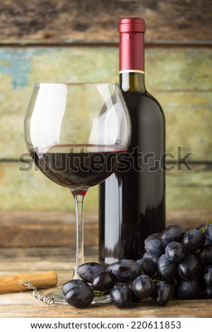 Winery background. Dark blue grapes with bottle of red wine and glass on wooden background - stock photo
