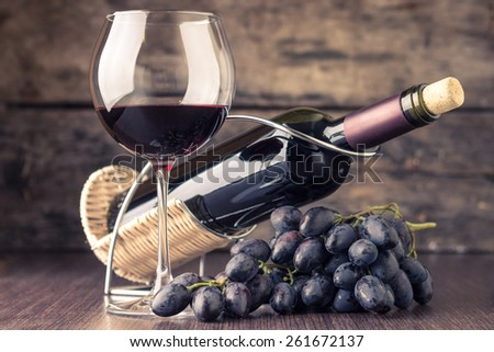Winery background. Wineglass with bottle of red wine and cluster of grape on wooden table. Toned image - stock photo