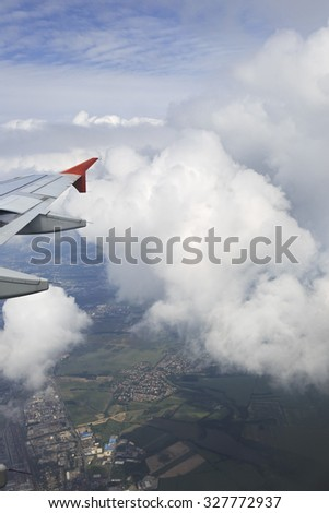 Wing aircraft and cumulus clouds in the sky above the earth. - stock photo