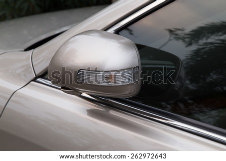 wing mirror of a bronze  car under sunset - stock photo