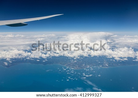 Wing of airplane flying above the clouds in the sky and ocean with land are below - stock photo