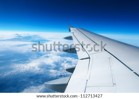 Wing of an airplane flying above the clouds. people looks at the sky from the window of the plane, using air transport to travel. - stock photo