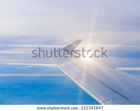 Wing of an airplane flying above the clouds. people looks at the sky from the window of the plane - stock photo