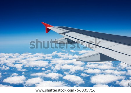 wing of the airplane under the clouds - stock photo