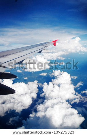 Wing of the plane on sky background - stock photo