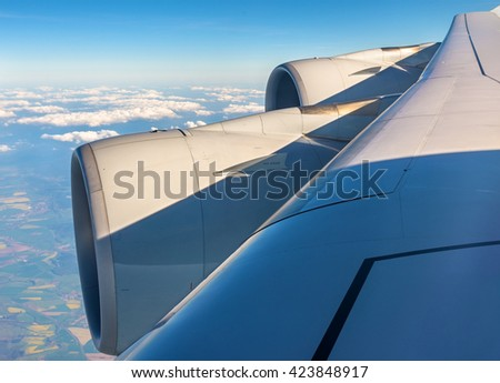 Wing with engines of Airbus A380 airliner flying over clouds - stock photo