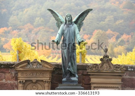 Winged angel standing guard in cemetery with landscape of vineyards, Germany. - stock photo