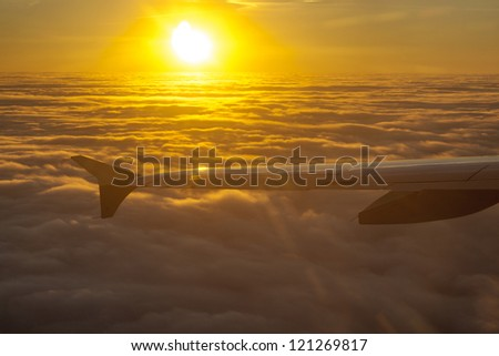 wings of aircraft in sunrise - stock photo