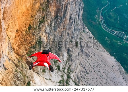 Wingsuit B.A.S.E. jumper jumps off a cliff in Italy - stock photo