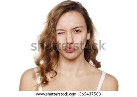 winking young woman without make-up with pursed lips - stock photo