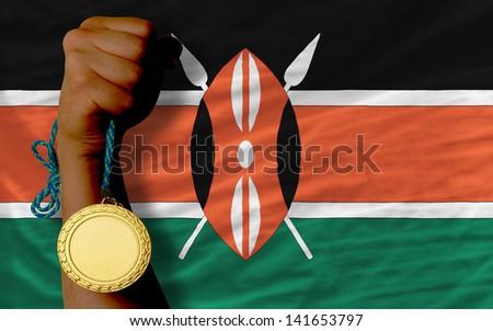 Winner holding gold medal for sport and national flag of kenya - stock photo
