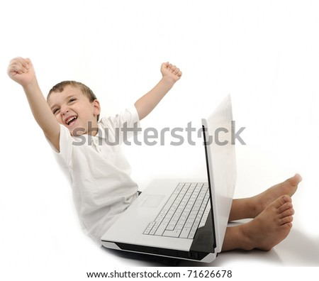 Winner little boy sitting with laptop isolated on white - stock photo