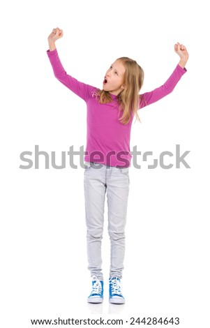 Winner little girl. Shouting young girl raising arms and looking away. Full length studio shot isolated on white. - stock photo