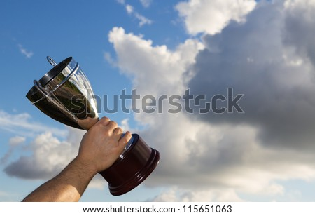 Winner with cup in hand to the sky - stock photo