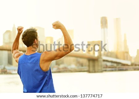Winning cheering success fitness runner man in New York City skyline celebrating happy and flexing strong muscles after running workout training outside with Brooklyn Bridge in background. - stock photo