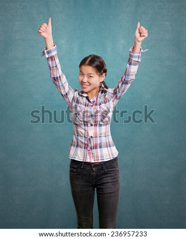 Winning concept. Asian girl shows well done with both hands - stock photo