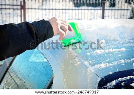 Winter and car. Person remove snow from car. Car covered with snow and ice.  - stock photo