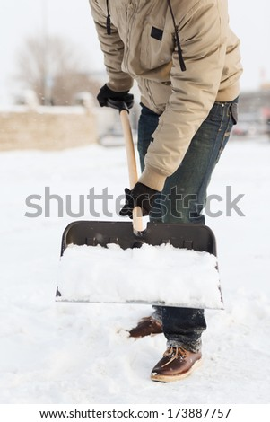 winter and cleaning concept - closeup of man shoveling snow from driveway - stock photo