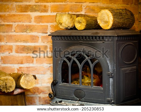 Winter at home. Closeup of fireplace with fire flame and firewood interior. Heating. - stock photo