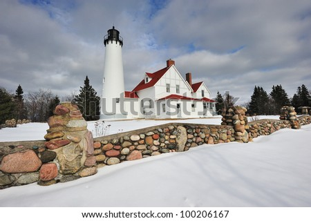 Winter at Point Iroquois Lighthouse - Whitefish Bay, Michigan USA Beautiful field-stone fence in the foreground. - stock photo