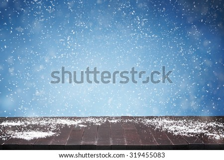 Winter background, close up of empty wooden table, desk and falling snow in the back with copy space - stock photo