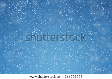 Winter background. Falling snow over blue background with copy space - stock photo