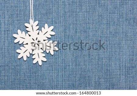 winter background: snowflake  on  jeans  fabric - stock photo