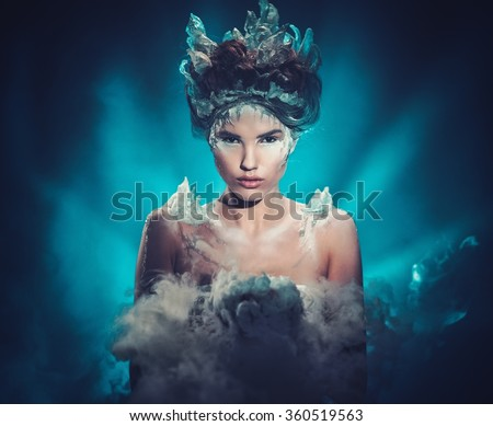 Winter beauty fantasy woman portrait. Beautiful young model girl with frozen fashion makeup and hairstyle. - stock photo