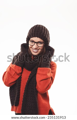 Winter beauty with a pretty young woman wearing glasses dressed in a trendy brown winter ensemble with gloves, hat and scarf, standing smiling at the camera - stock photo