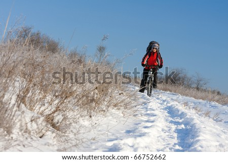 Winter biking at snow-covered field - stock photo