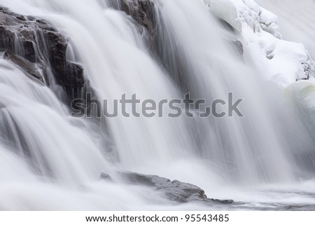 Winter, Bond Falls cascade captured with motion blur and framed by ice and snow, Michigan's Upper Peninsula, USA - stock photo