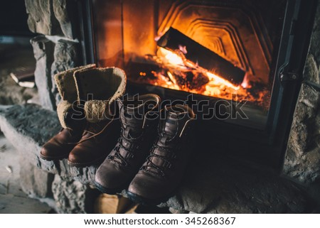 Winter boots in front of a fireplace. Family vintage folk boots drying near the fireside. Warm cozy fireplace in the authentic chalet. Hipster shoes getting warm near the burning fire in a cabin.  - stock photo