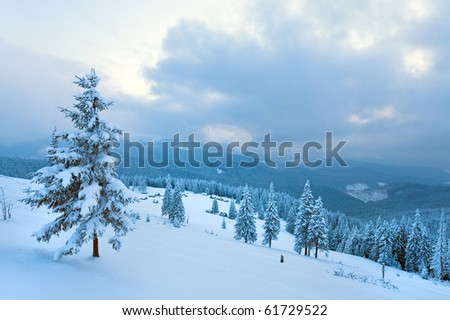 winter calm overcast mountain landscape with sheds group and mount ridge behind (Carpathian Mountains, Ukraine) - stock photo