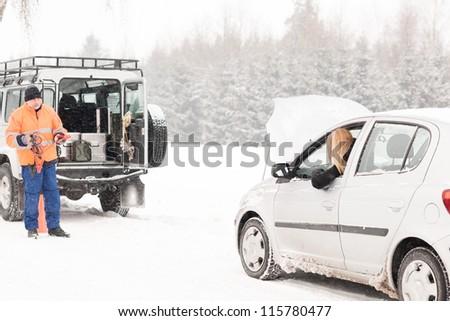 Winter car assistance man help woman breakdown snow road problem - stock photo