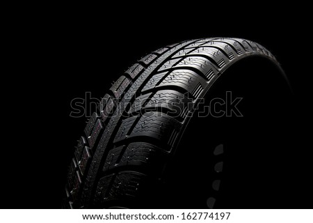 Winter Car tires close-up wheel profile structure on black background - stock photo