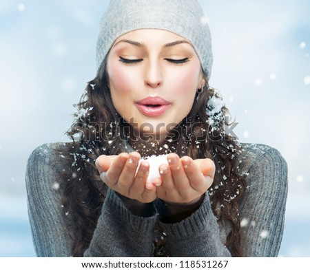 Winter Christmas Girl. Beautiful Woman Blowing Snow - stock photo
