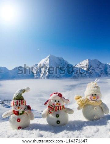 Winter, Christmas - happy snowman friends, snowy mountains in background - stock photo