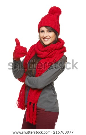 Winter, christmas, holidays concept. Happy smiling beautiful woman in red hat, scarf and mittens showing thumb up over white background - stock photo