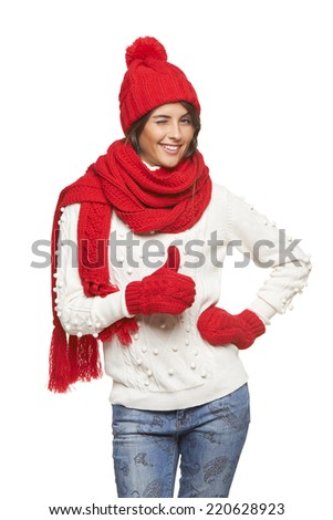 Winter, christmas, holidays concept. Smiling beautiful woman in red hat, scarf and mittens winking and gesturing thumb up, over white background - stock photo