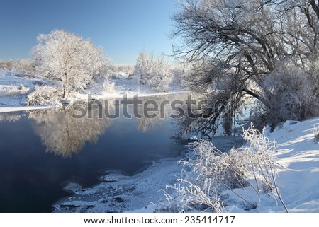 Winter christmas landscape with river and snow covered trees beautiful reflection in the water at very cold weather. Winter panorama at sunny day. - stock photo