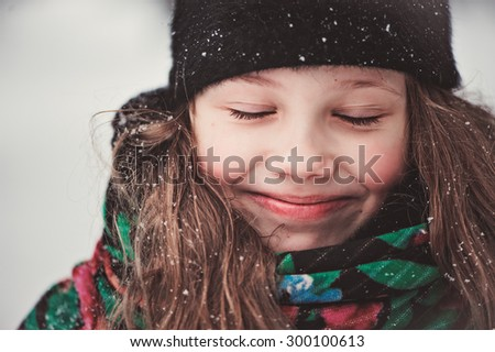 winter close up outdoor portrait of adorable happy child girl with closed eyes - stock photo