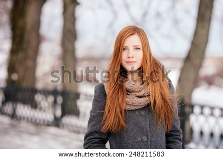 Winter closeup portrait of a cute redhead lady in grey coat and scarf strolling in the park - stock photo