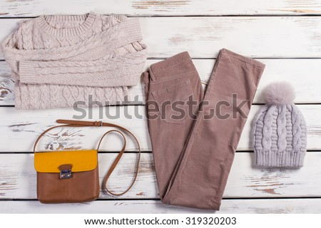 Winter clothes. Set of beautiful light women's clothing on a wooden background. - stock photo